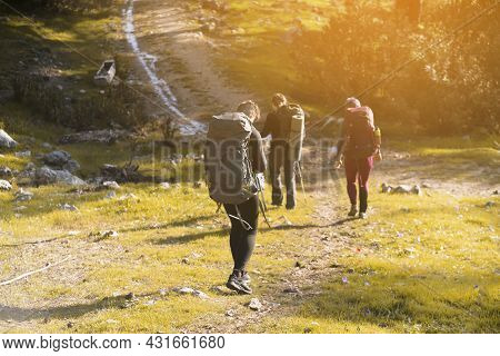 A Group Of Young Travelers Are Walking Along A Trail In The Mountains At Sunset. A Man And Two Girls