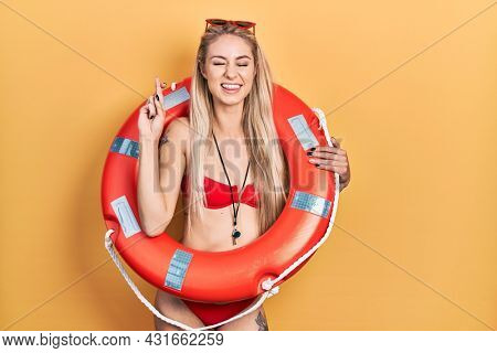 Young caucasian woman wearing bikini and holding lifeguard float gesturing finger crossed smiling with hope and eyes closed. luck and superstitious concept.