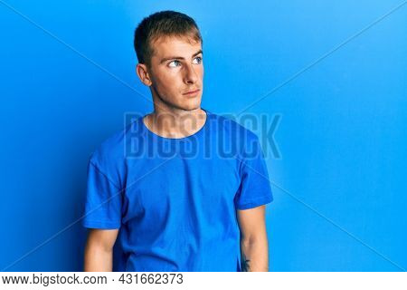 Young caucasian man wearing casual blue t shirt smiling looking to the side and staring away thinking.