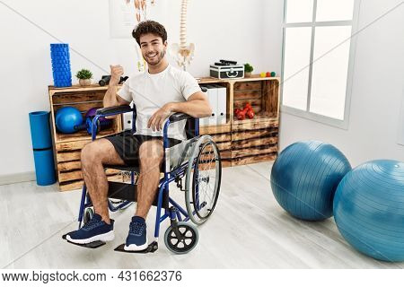 Hispanic man sitting on wheelchair at physiotherapy clinic smiling with happy face looking and pointing to the side with thumb up.