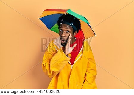 Young african american man wearing yellow raincoat hand on mouth telling secret rumor, whispering malicious talk conversation