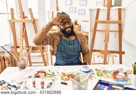 African american artist man at art studio very happy and smiling looking far away with hand over head. searching concept.