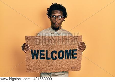 Young african american man holding welcome doormat making fish face with mouth and squinting eyes, crazy and comical.