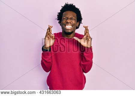 Young african american man wearing casual clothes gesturing finger crossed smiling with hope and eyes closed. luck and superstitious concept.