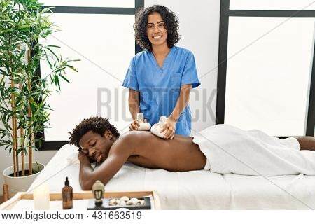 Young african american man reciving herbal pouches thai massage at beauty center.