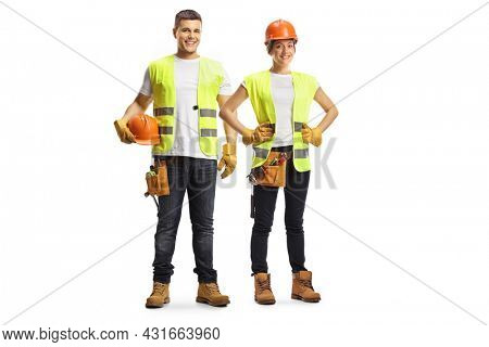 Full length portrait of a male and female construction workers wearing hardhats isolated on white background