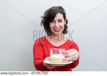 Smiling Brazilian Woman Holding And Offering A Cup Of Cappuccino.