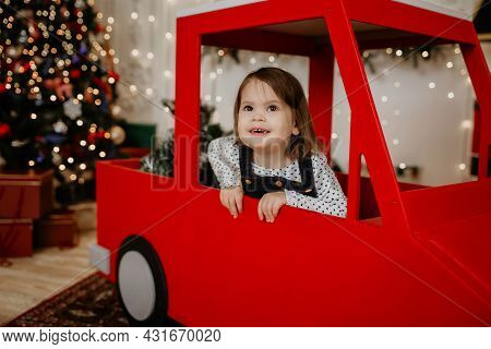 Little Girl Child Sits In A Red Toy Car On The Background Of A Christmas Tree And Smiles. New Year A