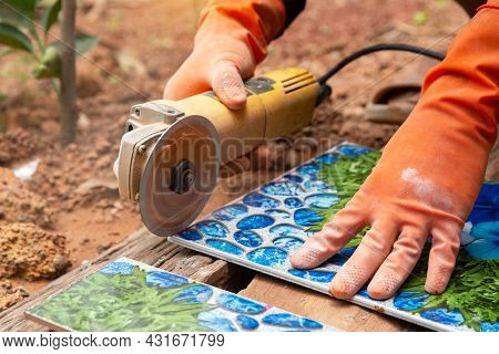 Construction Worker Wearing  Orange Rubber Gloves Was Cutting The Tiles With An Electric Grinder.