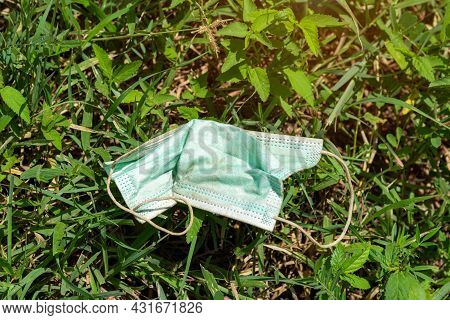 Thrown Away Or Lost Mouth Masks On The Ground In Grass, Outdoor,a Used, Blue Surgical Mask Used For