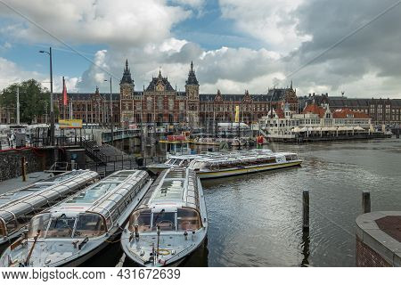 Amsterdam, Netherlands - August 14, 2021: Group Of Tourist Canal Boats Docked In Front Of Red And Go