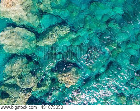 Azure water texture, transparent sea surface with a rocky bottom. Aerial view, Chora, agian Anna, Amorgos, natural blue background