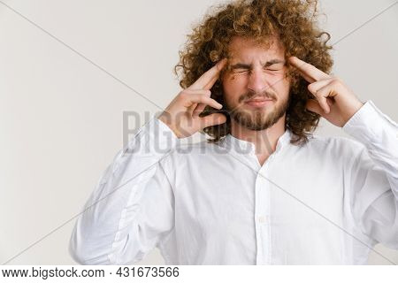 Young curly man with headache rubbing his temple and grimacing isolated over white background