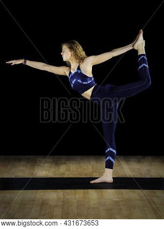 Female Instructor In A Yoga King Dancer Pose Variation At A Studio.
