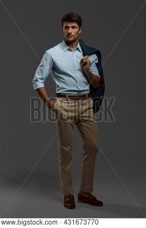 Young beautiful focused european businessman. Front view of bearded man with dark hair wear formal clothes. Isolated on dark gray background. Studio shoot. Copy space