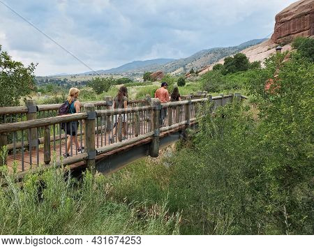 Five Young Hikers Cross Bridge On Red Rocks Trading Post Trail Near Morrison, Colorado Under Dramati