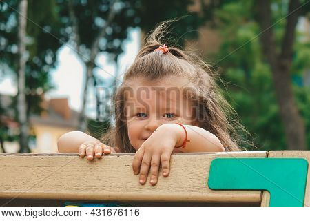 Kid On Obstacle Course. Pretty Happy Young Girl Playing Outside In Playground. Portrait Of Cute Girl