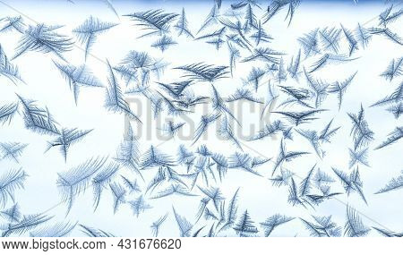 Beautiful frost patterns in the ice feather shape on frozen window as a symbol of Christmas wonder. Christmas or New year background.