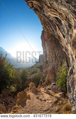A Girl Insures A Male Climber During Training. Family Vacation In Nature. Rock Climbing As A Sport A