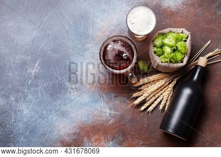 Lager beer mug, bottle, hops and wheat on old stone table. Top view flat lay with copy space
