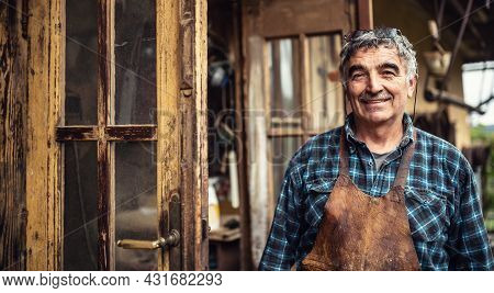 Aged Craftsman Standing And Smiling In Front Of His Rustic Workshop.