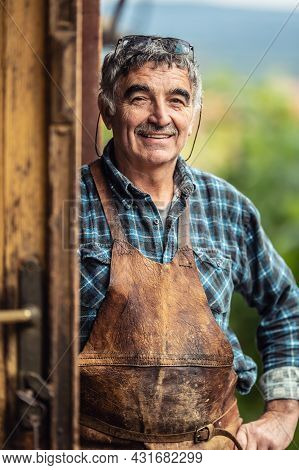 Older And Experienced Craftsman Stands Smiling In Front Of The Workshop In Checkered Shirt And Leath