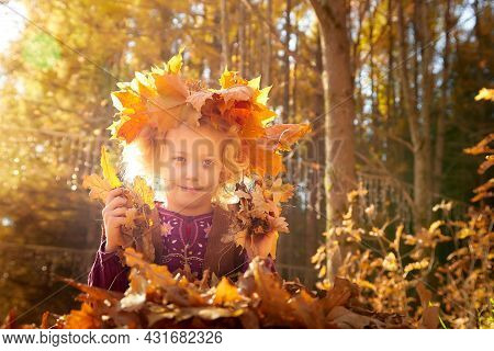 Portrait Of Young Little Girl With Blonde Curly Hair In An Autumn Park On A Yellow And Orange Leaf B