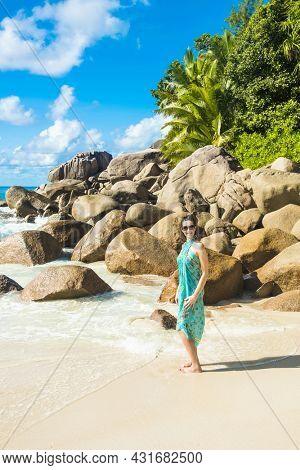 Beautiful young brunette in a white dress is sitting on a boulder located on the famous beach Anse Georgette in the Seychelles, island of Praslin