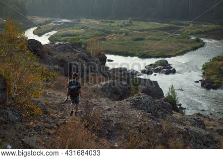 Guy Traveler Walks In The Mountains Near The River In Warm Sunny Weather. The Concept Of Youth And T