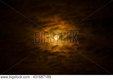 The Night Sky, Illuminated By The Light Of The Full Moon Behind The Clouds. The Blood Moon On Hallow