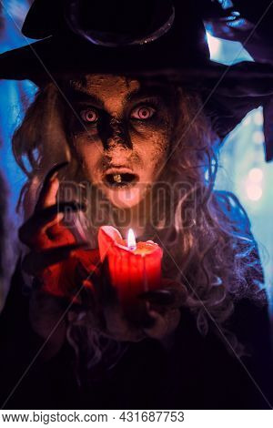 Scary tales. A scary ugly witch stands in an abandoned witch's den with a candle in her hands. Halloween.