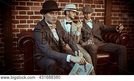 Three handsome men in elegant suits spends time in the men's club with cigars and whiskey. Luxury lifestyle. Men's beauty, fashion.