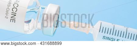 Vaccine vial with syringe isolated over blue background. Medical concept shows a medical vial and coronavirus vaccines coronavirus High quality photo