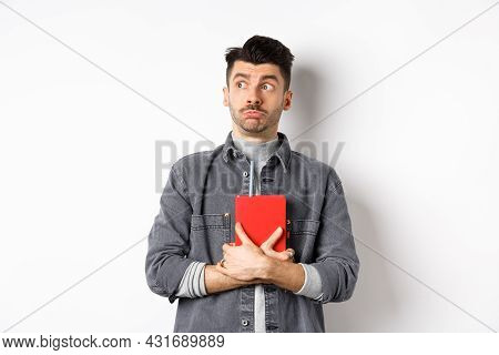 Silly Young Man Looking Aside At Logo With Timid Face, Holding His Diary Pressed To Chest, Carry Jou