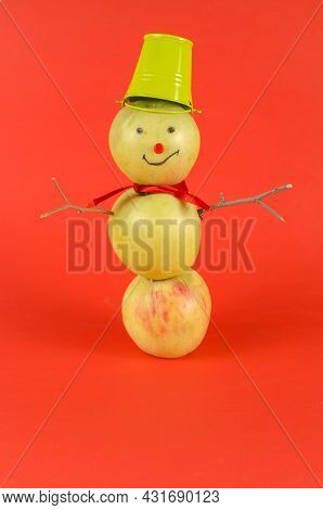 An Apple Snowman Standing On A Red Background. Creative Snowman Of Three Ripe Fruits With A Bucket O