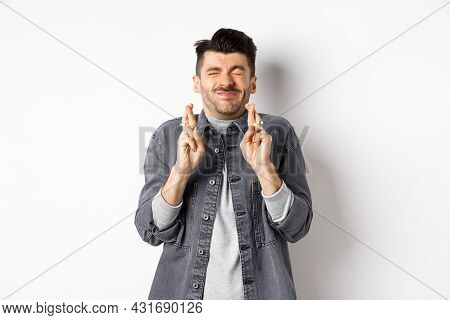 Hopeful Young Man Standing Nervous With Closed Eyes And Fingers Crossed, Making Wish, Begging God Fo