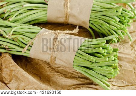 Bundles Of Raw Green Beans Against Brown Wrapping Paper. Two Bundles Of Bean Asparagus Wrapped With
