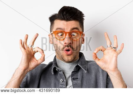 Funny Young Man In Stylish Glasses Squinting Eyes, Showing Okay Gesture, Recommend Eyewear Shop, Sta