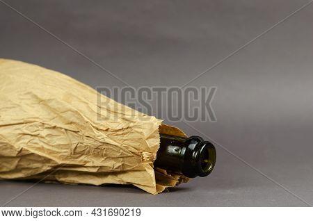 Drunken Bottle In Paper Bag Lies On Gray Background. Dark Empty Bottle Of Alcohol In Crumpled Brown