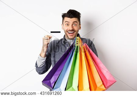 Happy Guy Shopaholic Holding Colorful Shopping Bags And Showing Plastic Credit Card, Smiling Excited