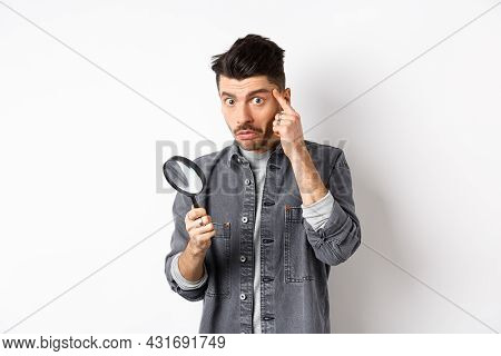 Confused Guy Found Something Down With Magnifying Glass, Look Puzzled At Camera, Standing Against Wh