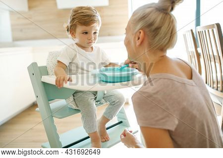 Mom Feeds The Baby. Young Woman Feeds Her Baby From A Spoon At Home. High Quality Photo.