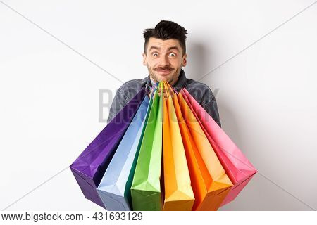 Excited Young Man Carry Colorful Shopping Bags And Smiling Happy, Shopper Buying On Sale, Standing O