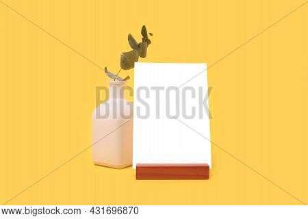 Eucalyptus Plant Twig And Paper Card Mockup In Front Of Yellow Background. Simplicity Concept With C
