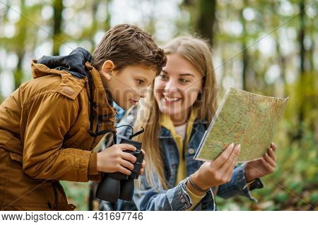 Happy Mother And Son Are Hiking In Forest. Boy Is Watching Nature With Binoculars.