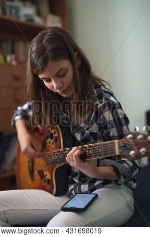 Teenage Girl Is Playing Guitar At Home.