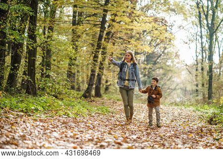 Happy Mother And Son Are Hiking In Forest.
