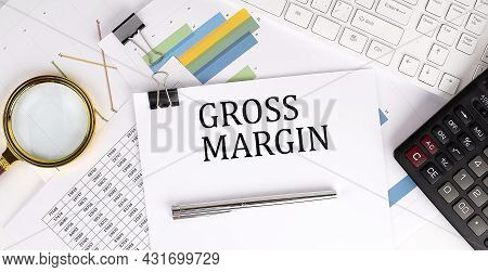 Gross Margin Text On The White Paper On Light Background With Charts Paper ,keyboard And Calculator