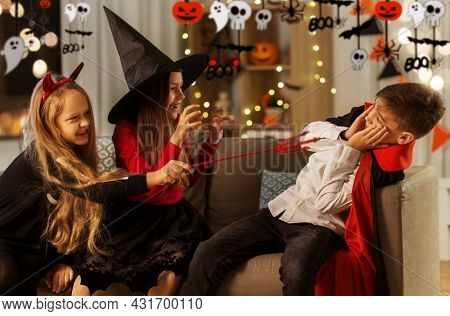 halloween, holiday and childhood concept - smiling boy and girls in party costumes playing and scaring each other at home at night decorated with garland and lights