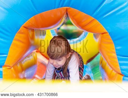 A Baby Girl Plays In An Inflatable Attraction In An Amusement Park. Cute Child On The Playground. An